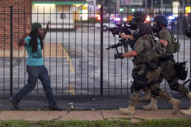 A man backs away as law enforcement officials close in and eventually detain him. He was part of the protests over the death of Michael Brown, an unarmed black teenager killed by a police officer, in Ferguson, Mo.