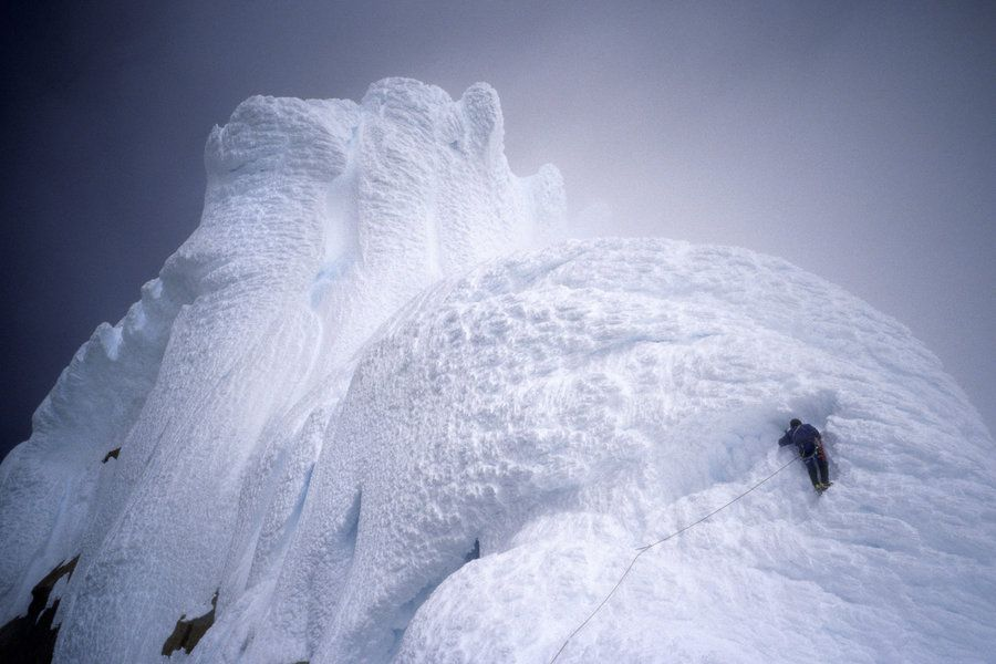 A climber surmounts a snow mushroom on Cerro Torre's west ridge, during an ascent of that peak in Argentine Patagonia.